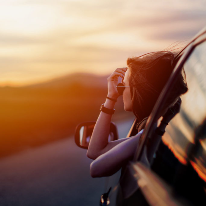 Beautiful young woman sitting in the car on the country road  and looking at the view on a beautiful sunny spring day